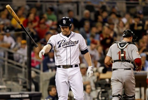 San Diego Padres' Chase Headley throws his bat as Houston Astros catcher Chris Snyder heads to dugout after Headley struck out with a runner in scoring position to end the sixth inning of a baseball game, Monday, July 16, 2012, in San Diego. The Padres had managed only three hits through six innings. (AP Photo/Lenny Ignelzi)