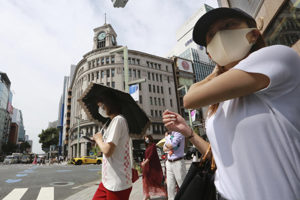 People wearing face masks to help protect against the spread of the coronavirus walk on a street in Tokyo Monday, Aug. 23, 2021. (AP Photo/Koji Sasahara)