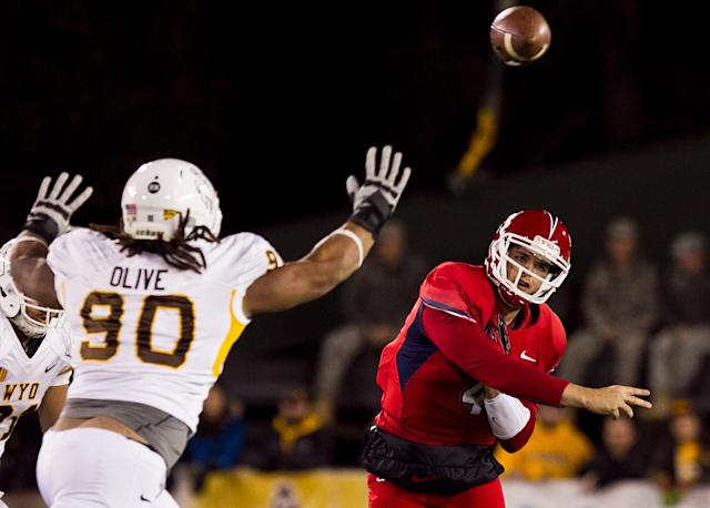 Fresno State quarterback Derek Carr (4) throws a pass past Wyoming defensive end Uso Olive (90) Saturday Nov. 9, 2013 during the first half of the game at War Memorial Stadium in Laramie, Wyo. (AP Photo/Jeremy Martin)