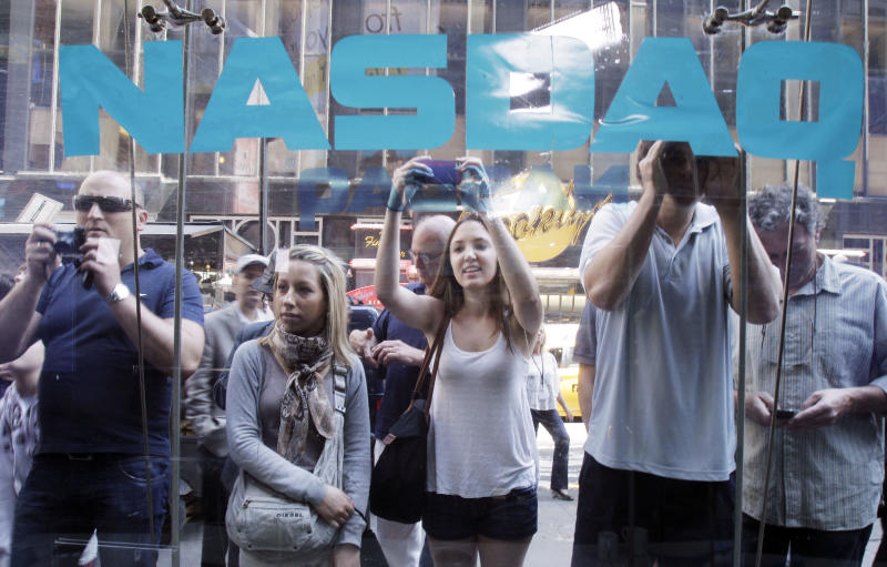 FILE - In a Friday, May 18, 2012 file photo, curious bystanders watch through the Nasdaq windows as Facebook shares begin trading, in New York. Facebook's stock is sinking nearly 7 percent, Monday, May 21, 2012, falling below the $38 IPO price, in the social network's second day of trading as a public company. (AP Photo/Richard Drew, File)