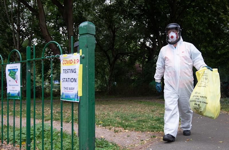 A worker for Leicester City Council carries a bag of clinical waste away from a Covid-19 testing station at Spinney Hill Park in Leicester where localised coronavirus lockdown restrictions have been in place since June 29, with non-essential shops ordered to close and people urged not to travel in or out of the area. (Photo by Joe Giddens/PA Images via Getty Images)