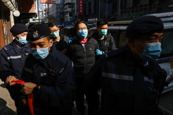 Daniel Wong is escorted by police as he returns to his office in Hong Kong