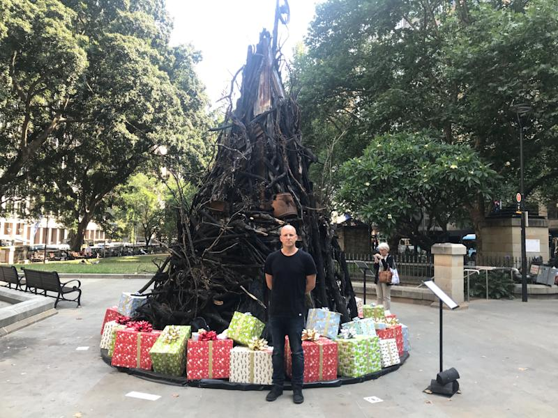 """Installation artist, James Dive, stands in front of """"Burnt Christmas tree"""" he built from charred logs and other bushfire remnants as a result of Australia's recent Bushfire crisis, in Sydney, Australia December 18, 2019. REUTERS/Jill Gralow (Photo: REUTERS)"""