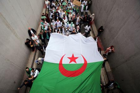 Health workers carry a national flag as they march during a protest calling on President Abdelaziz Bouteflika to quit, in Algiers
