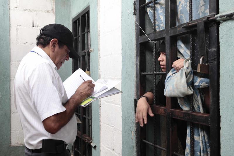 In this Jan. 24, 2013, an inmate in an isolation cell, right, talks to attorney Miguel Angel Ortiz, president of Conaprev, the national mechanism to prevent torture, at the prison in Comayagua, Honduras. A year after one of the century's worst prison fires killed more than 350 people, the investigation remains open and prosecutors have filed no charges. The burned cells and electrical system are still being repaired. Even the inmate who was the hero of the fire, finding keys and freeing hundreds of men, was never pardoned as President Porfirio Lobo had promised. (AP Photo/Alberto Arce)