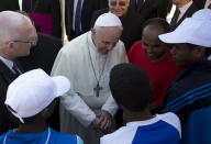 """FILE - In this July 8, 2013 file photo, Pope Francis speaks to migrants, some wearing white caps, during his visit to the island of Lampedusa, southern Italy. Pope Francis on Thursday, May 6, 2021 denounced """"aggressive"""" nationalism that rejects migrants and demanded that Catholics follow the Gospel-mandated call for an inclusive, welcoming church that doesn't distinguish between """"natives and foreigners, residents and guests."""" (AP Photo/Alessandra Tarantino, pool )"""