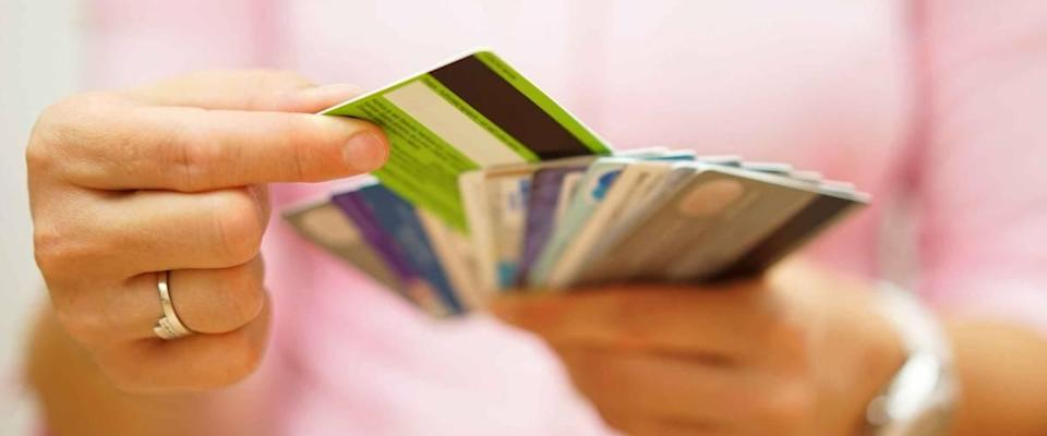 close up of woman's hands holding multiple credit cards fanned out