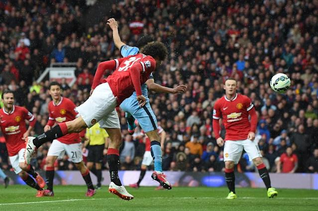 Manchester United's Belgian midfielder Marouane Fellaini (C) scores a goal during the English Premier League football match between Manchester United and Manchester City in Manchester, England, on April 12, 2015 (AFP Photo/Paul Ellis)