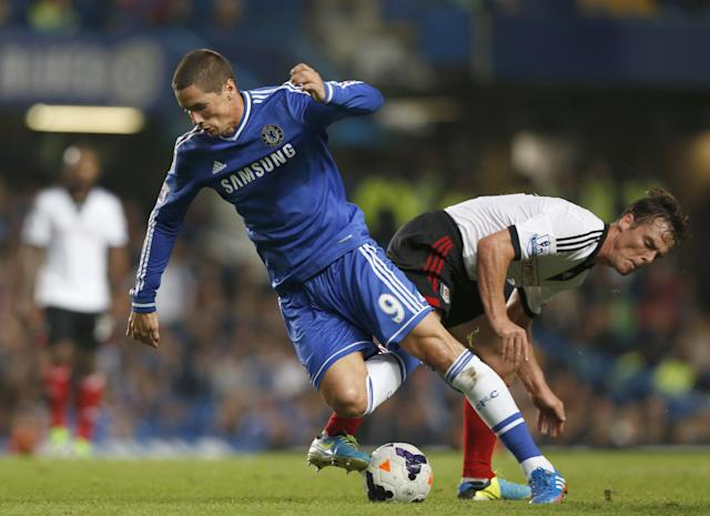 Chelsea's Fernando Torres, left falls as Fulham's Scott Parker tackles during the English Premier League soccer match between Chelsea and Fulham at Stamford Bridge, London, Saturday, Sept. 21, 2013. (AP Photo/Sang Tan)