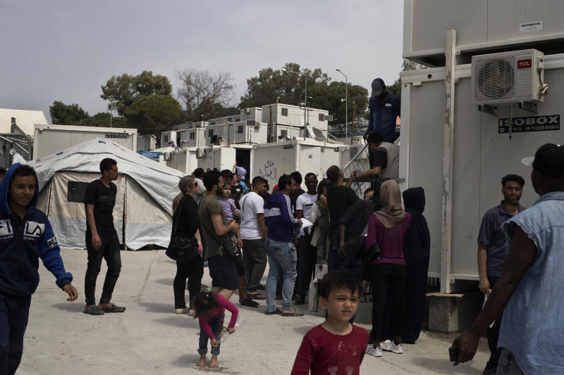 FILE - In this Friday, May 4, 2018 file photo, migrants and refugees wait outside the UNHCR offices for their papers, inside the camp of Moria, Lesbos island, Greece. European governments breathed a sigh of relief as the European Union reached a deal with Turkey designed to stop hundreds of thousands of refugees and migrants heading into the heart of Europe. For many of those who had fled war, hunger and poverty hoping for a bright future on the continent, the deal shattered their dreams. (AP Photo/Petros Giannakouris, File)