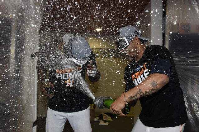 Houston Astros designated hitter Yordan Alvarez, left, and pitcher Hector Rondon, right, celebrate their win over the Tampa Bay Rays in Game 5 of a baseball American League Division Series in Houston, Thursday, Oct. 10, 2019. (AP Photo/Eric Christian Smith)