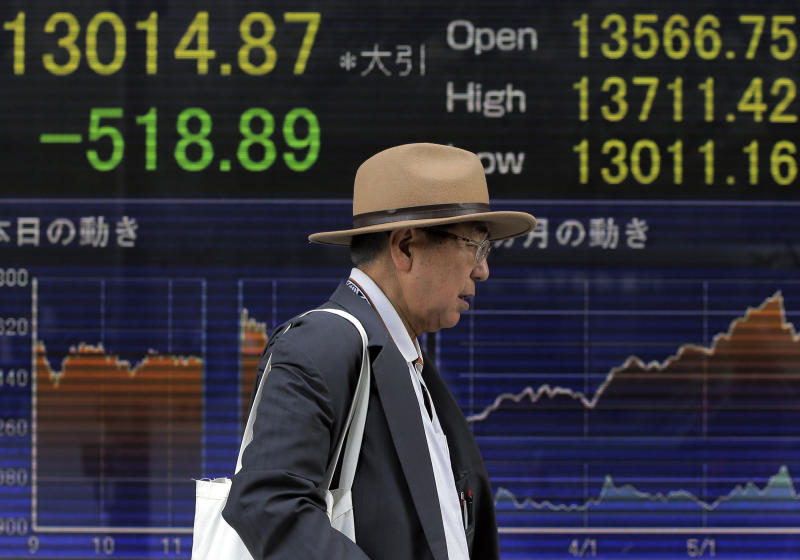 A man walks by an electronic stock board of a securities firm in Tokyo, Wednesday, June 5, 2013. Asian stock markets fell Wednesday as signs the U.S. Federal Reserve might scale back its super-loose monetary policy caused investors to trim equity investments. Japan's Nikkei 225 index tumbled 1.8 percent to 13,295.89, registering disappointment with a lack of detail in Prime Minister Shinzo Abe's unveiling of the third plank of his so-called Abenomics program intended to rouse a long-stagnant economy. (AP Photo/Itsuo Inouye)