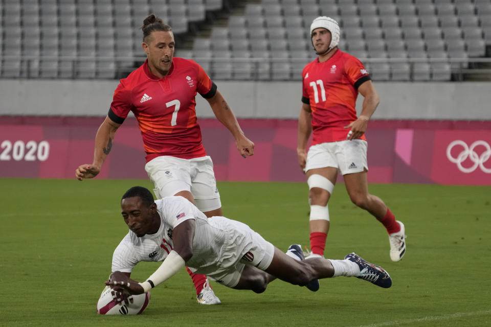 Perry Baker of the United States scores a try as Britain's Dan Bibby, left, and Ethan Waddleton look on, in their men's rugby sevens quarterfinal match at the 2020 Summer Olympics, Tuesday, July 27, 2021 in Tokyo, Japan. (AP Photo/Shuji Kajiyama)