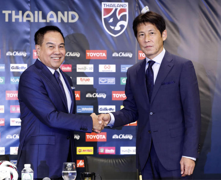Former Japan manager Akira Nishino, right, and Thai Football Association president Somyot Pumpanmuang shake hands during a press conference in Tokyo, Friday, July 19, 2019. Nishino was officially named head coach of the Thailand national and under-23 men's soccer teams on Wednesday. (Masanobu Kumagai/Kyodo News via AP)