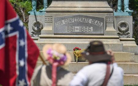 Charles Harper, right, and his wife Lulu, carry the Confederate battle flag in Brandenburg, Kentucky, U.S. May 29, 2017 in front of a Civil War Confederate Soldier Memorial recently removed from the campus of the University of Louisville. REUTERS/Bryan Woolston