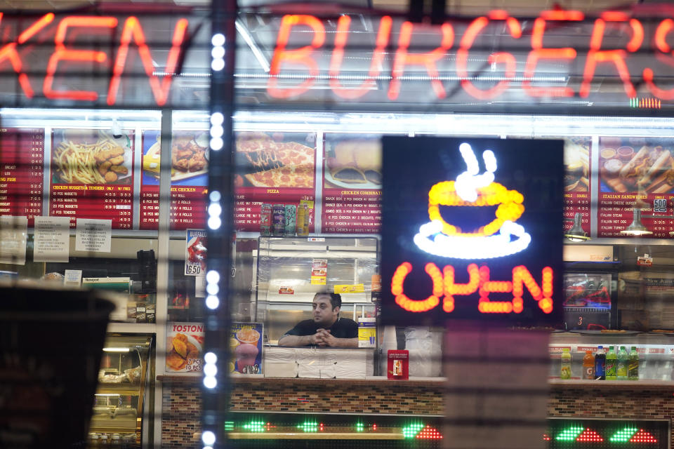 FILE - In this Nov. 12, 2020, file photo, an employee of a restaurant waits for customers in Newark, N.J. From New Mexico to New Jersey to Chicago, states and cities were ordering or imploring residents to stay home to help stem a rising tide of coronavirus infections that has prompted fears the nation's health care system will quickly be overwhelmed. (AP Photo/Seth Wenig, File)