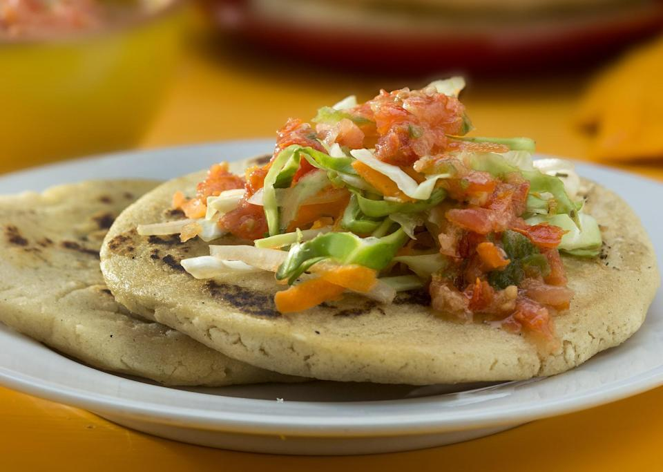 """<p>Making pupusas is easier than you may think. Top these cheese-stuffed food truck favorites with <a href=""""https://www.thedailymeal.com/recipes/curtido?referrer=yahoo&category=beauty_food&include_utm=1&utm_medium=referral&utm_source=yahoo&utm_campaign=feed"""" rel=""""nofollow noopener"""" target=""""_blank"""" data-ylk=""""slk:chopped cabbage"""" class=""""link rapid-noclick-resp"""">chopped cabbage</a>, vegetarian refried beans and salsa.</p> <p><a href=""""https://www.thedailymeal.com/recipes/pupusas?referrer=yahoo&category=beauty_food&include_utm=1&utm_medium=referral&utm_source=yahoo&utm_campaign=feed"""" rel=""""nofollow noopener"""" target=""""_blank"""" data-ylk=""""slk:For the Pupusas recipe, click here."""" class=""""link rapid-noclick-resp"""">For the Pupusas recipe, click here.</a></p>"""