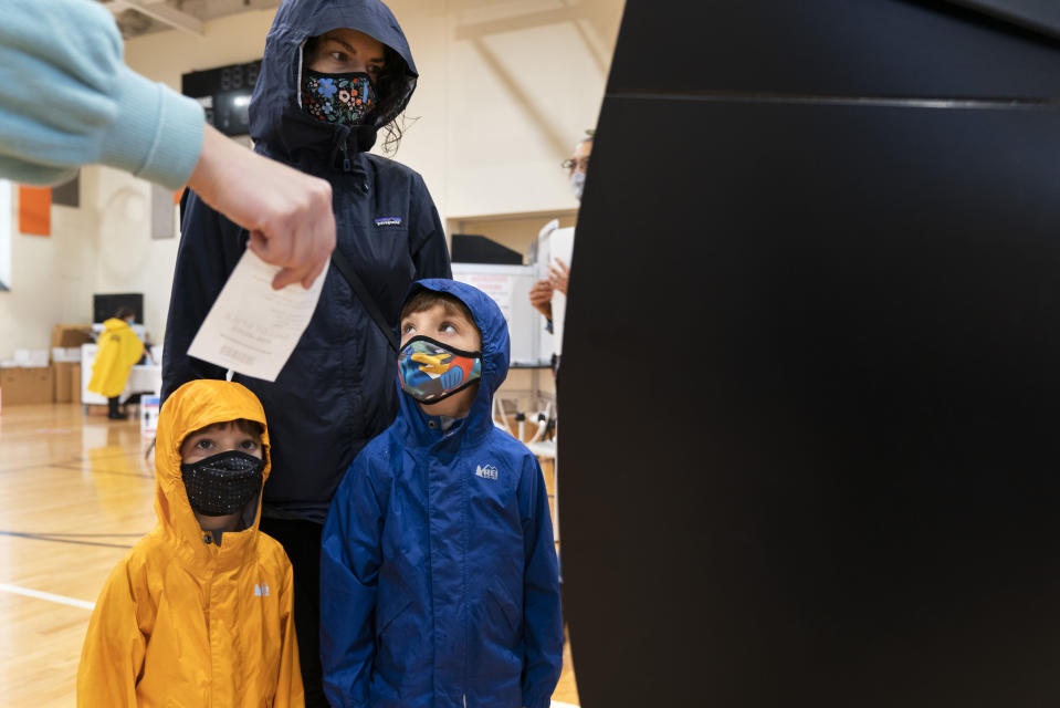 """A poll worker assists Rachael Friedlander, of Washington, to vote with her sons, Shay Burke, 4, left, and Julian Burke, 6, right, at an early voting center at Ida B. Wells Middle School, Thursday, Oct. 29, 2020, in Washington. The family was wearing raincoats due to pouring rain outside. """"I've brought my kids with me to vote in every election since they were born,"""" says Friedlander, """"I want to teach them the power we have to make informed choices about what we want for our community and our country. It is the most important thing we can do as citizens."""" (AP Photo/Jacquelyn Martin)"""
