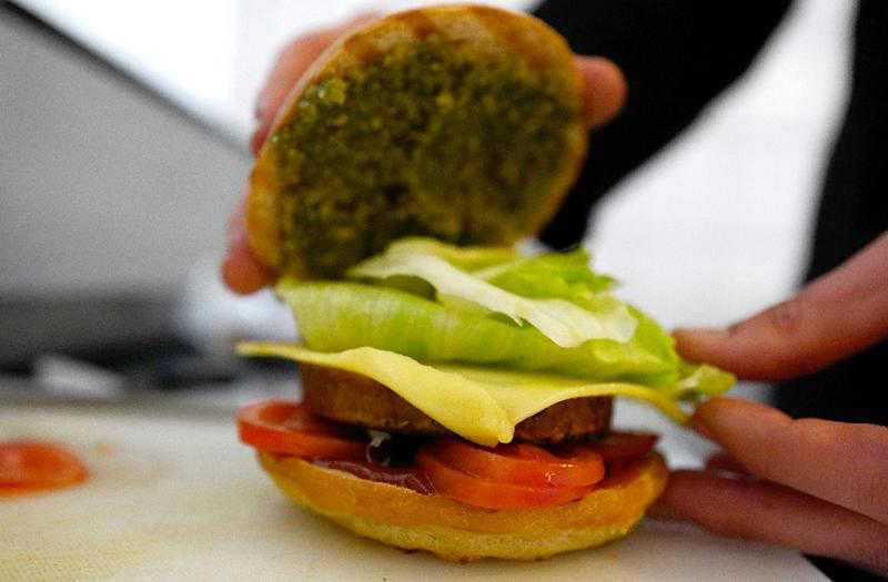 Chef Johannes Thenerl prepares a vegan burger using a patty made of wild garlic at vegan restaurant L'Herbivore in Berlin (AFP Photo/John Macdougall)