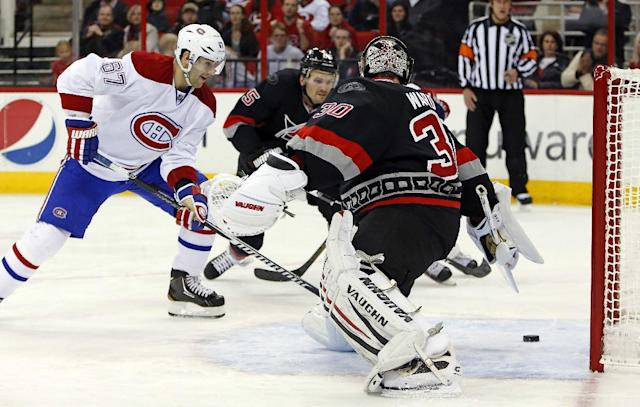 Montreal Canadiens' Max Pacioretty (67) slips the puck past Carolina Hurricanes goalie Cam Ward (30) for a goal during the first period of an NHL hockey game in Raleigh, N.C., Tuesday, Dec. 31, 2013. (AP Photo/Karl B DeBlaker)