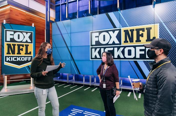 Fox NFL Kickoff director Courtney Stockmal, left, speaks to other producers in the show's studio.