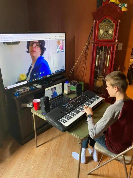 Boy with disability learning to play piano on zoom call with teacher