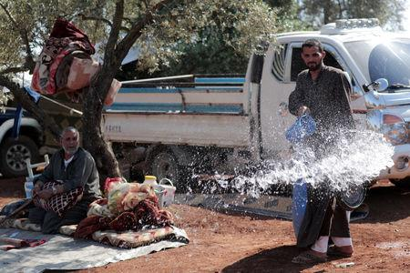 FILE PHOTO: Ahmen al-Hussein, 32, a displaced Syrian pours water in an olive grove in the town of Atmeh, Idlib province, Syria May 19, 2019. REUTERS/Khalil Ashawi