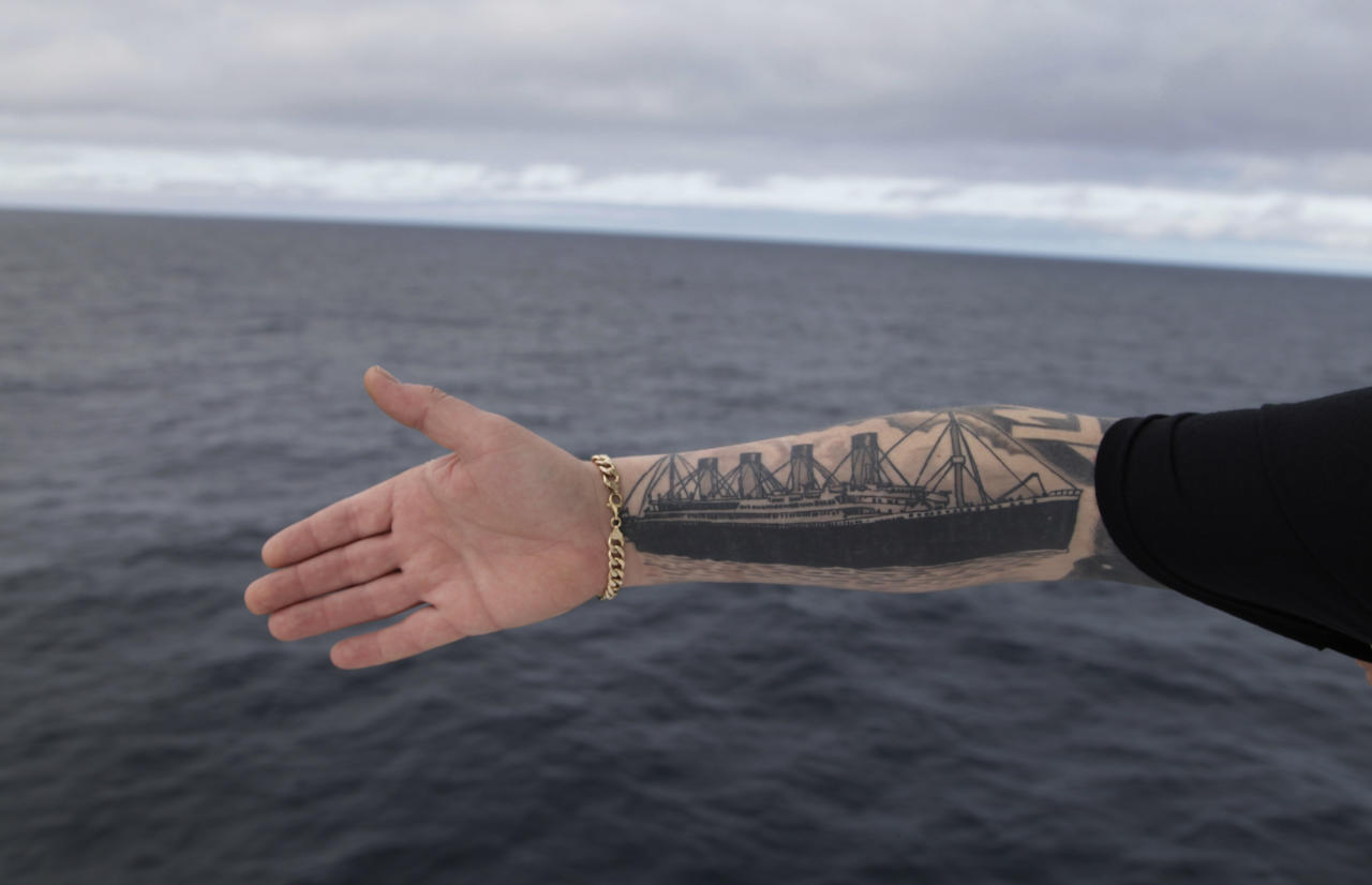 Derek Chambers from Belfast shows his tattoo of the Titanic, aboard the MS Balmoral Titanic memorial cruise ship in the Atlantic Ocean, Thursday, April 12, 2012. Nearly 100 years after the Titanic went down, the cruise with the same number of passengers aboard is setting sail to retrace the ship's voyage, including a visit to the location where it sank. The Titanic Memorial Cruise departed Sunday, April 8, from Southampton, England, where the Titanic left on its maiden voyage and the 12-night cruise will commemorate the 100th anniversary of the sinking of the White Star liner. With 1,309 passengers aboard, the MS Balmoral will follow the same route as the Titanic and organizers are trying to recreate the onboard experience minus the disaster from the food to a band playing music from that era. (AP Photo/Lefteris Pitarakis)