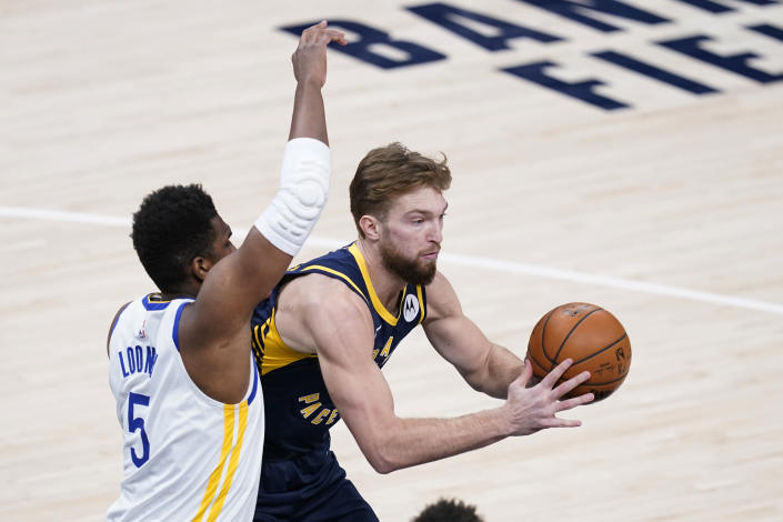 Indiana Pacers' Domantas Sabonis, right, passes the ball as Golden State Warriors' Kevon Looney (5) defends during the first half of an NBA basketball game Wednesday, Feb. 24, 2021, in Indianapolis. (AP Photo/Darron Cummings)