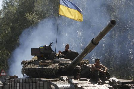 Ukrainian soldiers ride on a tank as they patrol area near eastern Ukrainian town of Debaltseve