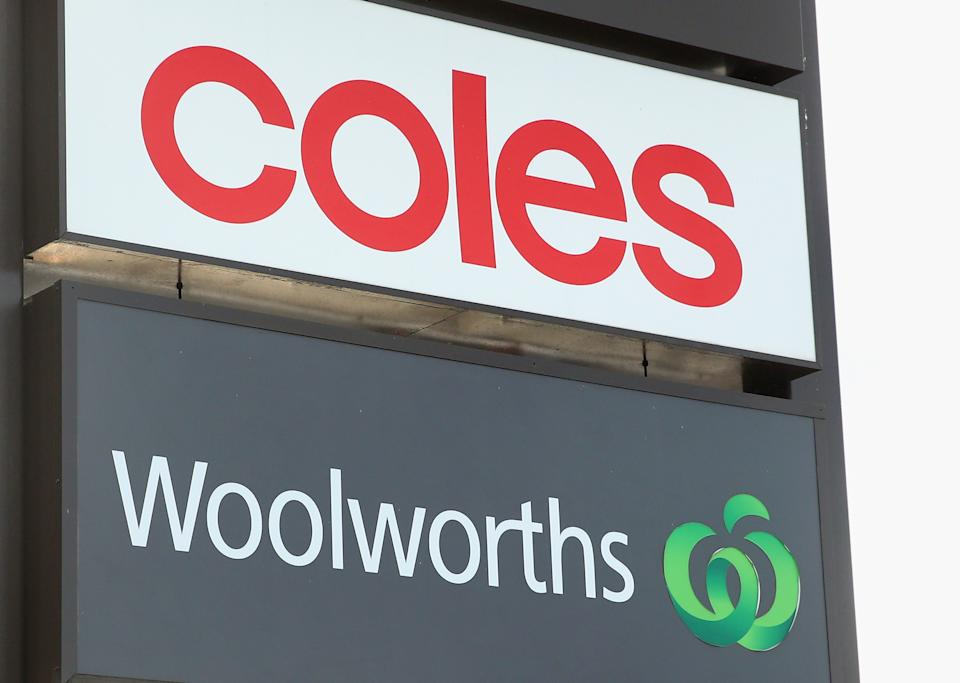 Coles and Woolworths signs sit atop one another. Source: Getty Images