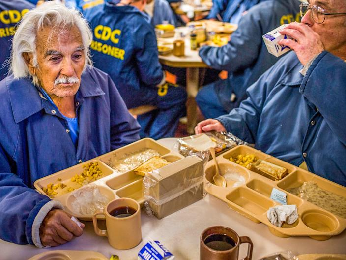 SAN LUIS OBISPO, CA - DECEMBER 19: (Editorial Use Only) Anthony Alvarez (L), age 82, eats breakfast with Phillip Burdick, a fellow prisoner and member of the Gold Coats program at California Men's Colony prison on December 19, 2013 in San Luis Obispo, California. The Gold Coats program is a volunteer care program where healthy prisoners volunteer to take care of elderly prisoners who either need general assistance with mobility and every day life or who also struggle with Alzheimer's and dementia. T(Photo by Andrew Burton/Getty Images)