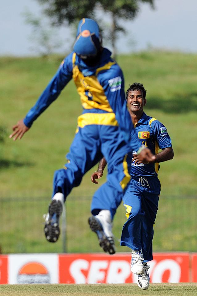Sri Lankan cricketers Nuwan Kulasekara (R) and Kushal Janith Perera celebrate the dismissal of Bangladeshi cricketer Mohammad Ashraful during the opening one-day international (ODI) match between Sri Lanka and Bangladesh at The Suriyawewa Mahinda Rajapakse International Cricket Stadium in the southern district of Hambantota on March 23, 2013. Sri Lankan cricket captain Angelo Mathews won the toss and elected to field. AFP PHOTO/ Ishara S. KODIKARA (Photo credit should read Ishara S.KODIKARA/AFP/Getty Images)