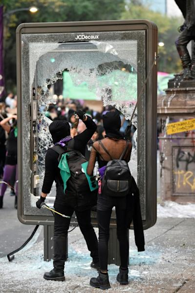 Activists break an advertising sign as they protest on International Day for the Elimination of Violence Against Women, in Mexico City, on November 25, 2019