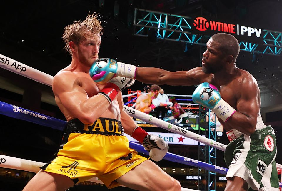MIAMI GARDENS, FLORIDA - JUNE 06: Floyd Mayweather (R) punches Logan Paul during their contracted exhibition boxing match at Hard Rock Stadium on June 06, 2021 in Miami Gardens, Florida. (Photo by Cliff Hawkins/Getty Images)