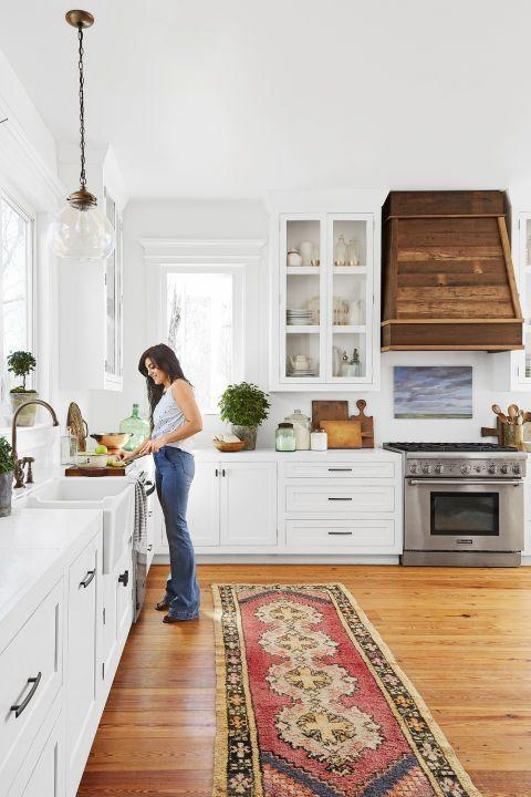 """<p>The salvaged wood hood, custom-built by the owner of this <a href=""""https://www.countryliving.com/home-design/house-tours/g4441/mississippi-farmhouse/"""" rel=""""nofollow noopener"""" target=""""_blank"""" data-ylk=""""slk:Mississippi farmhouse"""" class=""""link rapid-noclick-resp"""">Mississippi farmhouse</a>, and a Turkish runner add warmth to the mostly white kitchen. We love the additional of a landscape painting floating above the range as an unexpected alternative to tile.</p>"""