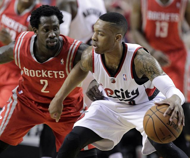 Portland Trail Blazers guard Damian Lillard, right, works against Houston Rockets guard Patrick Beverley during the first half of Game 3 of an NBA basketball first-round playoff series in Portland, Ore., Friday, April 25, 2014. (AP Photo/Don Ryan)