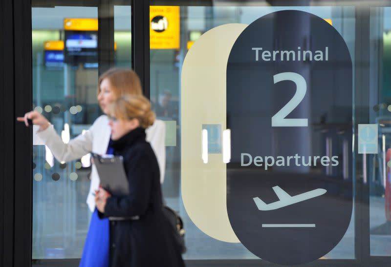 FILE PHOTO: Visitors are seen in a doorway at the departure area of the new 'Terminal 2: The Queen's Terminal' during a media event in Heathrow Airport, west London