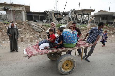 A displaced Iraqi family is transported on a cart as the battle between the Iraqi Counter Terrorism Service and Islamic State militants continues nearby, in western Mosul