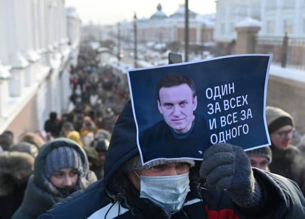 """A man holds a placard reading """"One for all, all for one"""" during a rally in support of Russian opposition leader Alexei Navalny in Omsk, Russia, January 23, 2021."""