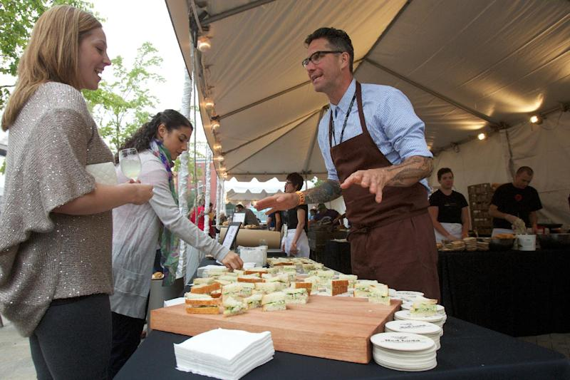 In this Sept. 20, 2012 photo, Jason French of the Ned Ludd restaurant serves shrimp and watercress tea sandwiches during the Feast Portland food festival in Portland, Ore. Far from the expectant gaze of major restaurant critics and the accompanying pressure to produce the Next Big Thing, the little-big city of Portland offers chefs a unique opportunity - the chance to experiment. (AP Photo/The Oregonian, Doug Beghtel)