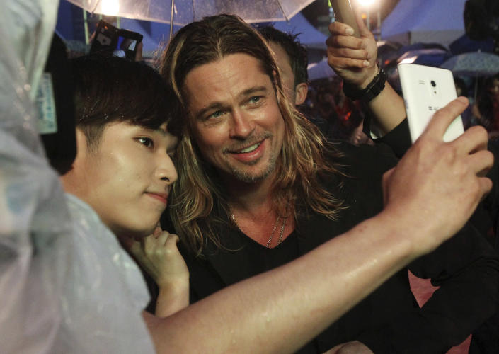 """File - In this Tuesday, June 11, 2013 file photo U.S. actor Brad Pitt poses for a photo with a fan upon arrival at the South Korea premiere of his latest film """"World War Z"""" in Seoul. """"Selfie"""" the smartphone self-portrait has been declared word of the year for 2013 by Britain's Oxford University Press. (AP Photo/Ahn Young-joon, File)"""