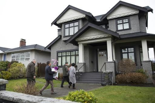 Individuals with flowers exiting from a vehicle with consular plates arrive at the residence of Huawei Technologies Chief Financial Officer Meng Wanzhou after she was released on bail in Vancouver, British Columbia