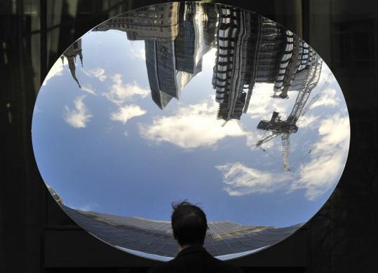 A city worker views buildings including the Lloyds building, reflected in the sculpture 'Sky Mirror' by Anish Kapoor in the financial district of the City of London, December 7, 2011.