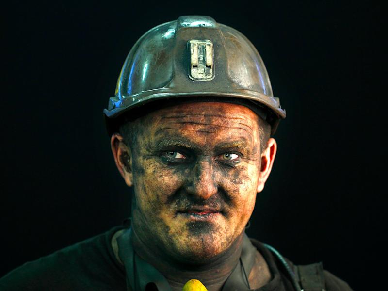 Coal miner Miroslaw Blasiak, a combine operator, poses for a photograph following his shift at Zofiowka coal mine of the JSW coal mine company, in Jastrzebie Zdroj, southern Poland September 27, 2012. State-controlled JSW, the biggest coking coal producer in the European Union, risks making an unexpected net loss in the third quarter and remaining in the red for the full year due to slumping coal prices, its chief executive said August 1, 2013. The company had undertaken several steps to counter the fall in prices, aiming to lower costs by up to 200 million zlotys ($62 million) by the end of this year. JSW has cut capital investment and plans to cut labour costs further. The management board is negotiating with unions to freeze wages for a year and wants cut some employee benefits. TO GO WITH STORY POLAND-JSW/ Photo taken September 27, 2012.