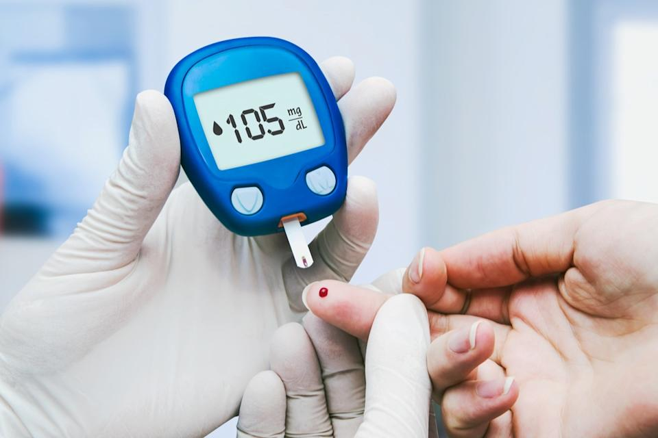 Doctor making blood sugar test in clinic for diabetes
