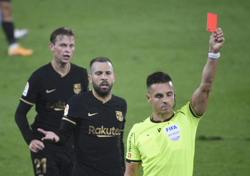 Barcelona's Spanish defender Jordi Alba (2L) reacts to Spanish referee Carlos del Cerro presenting a red card to Barcelona's French defender Clement Lenglet (out of frame) during the Spanish league football match RC Celta de Vigo against FC Barcelona at the Balaidos stadium in Vigo on October 1, 2020. (Photo by MIGUEL RIOPA / AFP) (Photo by MIGUEL RIOPA/AFP via Getty Images)