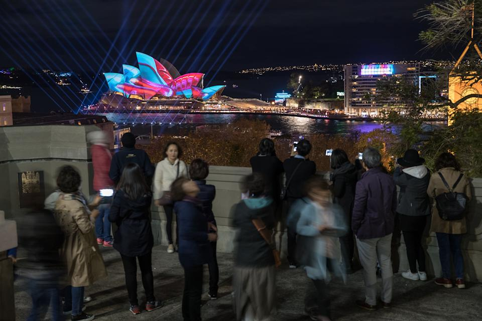 SYDNEY, AUSTRALIA - JUNE 06:  Tourists look over the city as the Sydney Opera House sails and surrounds are lit as part of the Vivid Festival on June 6, 2017 in Sydney, Australia. Vivid Sydney is an annual festival that features light sculptures and installations throughout the city. The festival takes place May 26 through June 17.  (Photo by Mark Kolbe/Getty Images)