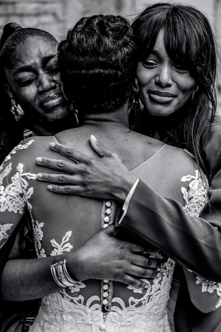 Two women cry as they hug a bride.