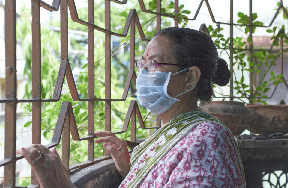 An aged Indian woman looking out of verandah in her house, wearing face mask during coronavirus lockdown in Kolkata. Concept of home isolation in fight against coronavirus. Photo taken in Kolkata on 04/26/2020.